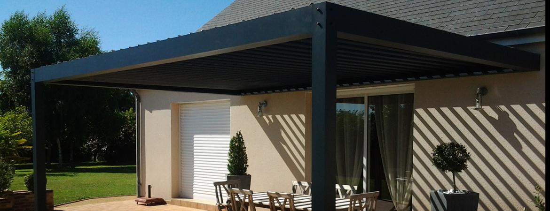 Pergola bioclimatique avec lames orientables, installée contre une maison