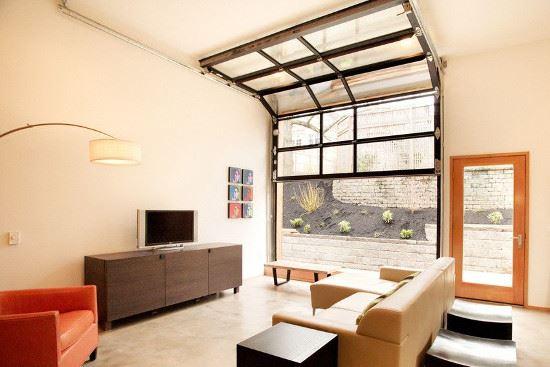 Porte de garage sectionnelle dans un salon pour une ouverture vers l'extérieur